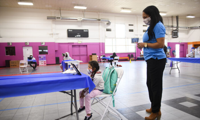 A YMCA staff member assists a child as they attend online classes at a learning hub inside the Crenshaw Family YMCA, as schools remain closed to in-person instruction, in Los Angeles, Calif., on Feb. 17, 2021. (Patrick T. Fallon/AFP via Getty Images)