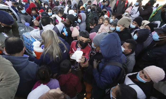 Migrants receive food as they wait for news at the border, in Tijuana, Mexico, on Feb. 19, 2021. (Gregory Bull/AP Photo)