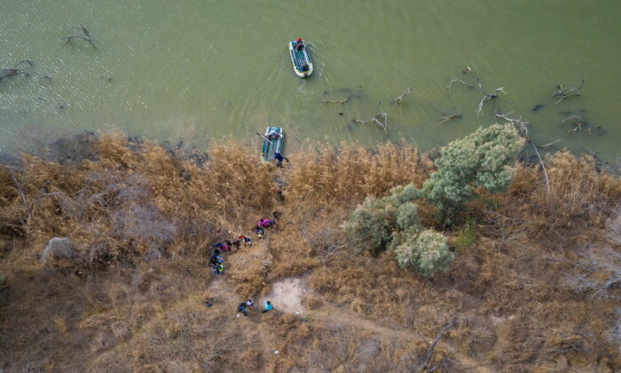 Illegal immigrants climb the banks of the Rio Grande River into the United States as smugglers on rafts prepare to return to Mexico in Penitas, Texas, on March 5, 2021. (Adrees Latif/Reuters)