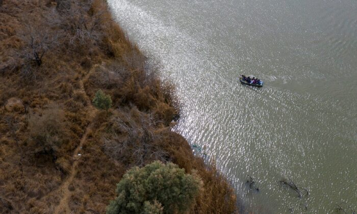 Smugglers use a raft to transport immigrant families and children across the Rio Grande River into the United States from Mexico in Penitas, Texas, on March 5, 2021. (Adrees Latif/Reuters)