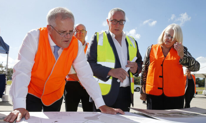 Prime Minister Scott Morrison is seen inspecting plans with Mark Chilcott of Energy Renaissance, and Industry Minister Karen Andrews during a recent visit to their site in Tomago, NSW, on March 4, 2021. (AAP Image/Darren Pateman)