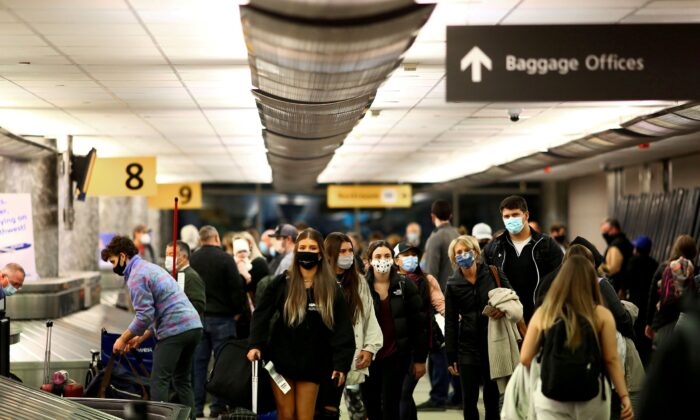 Travelers wearing protective masks reclaim their luggage at the airport in Denver, Colorado, on Nov. 24, 2020. (Kevin Mohatt/Reuters File Photo)
