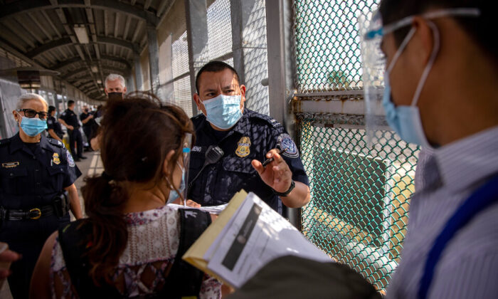 A Customs and Border Protection officer speaks with immigrants at the U.S.–Mexico border in Matamoros, Mexico, on Feb. 25, 2021. (John Moore/Getty Images)