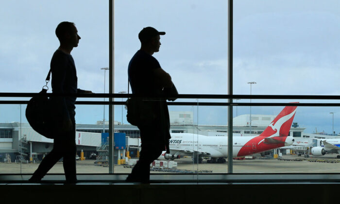 Two passengers walk past a Qantas jet at the International terminal at Sydney Airport on March 10, 2020 in Sydney, Australia. (Mark Evans/Getty Images)