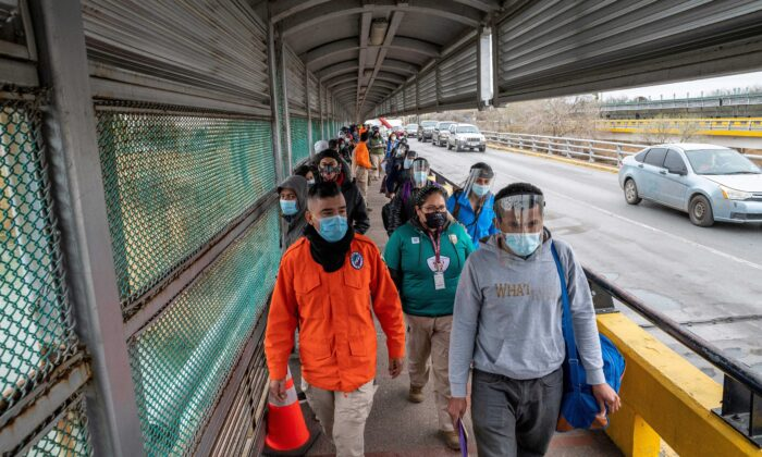 Migrants approach the U.S. border on Gateway International Bridge in Brownsville, Texas, on March 2, 2021. (Sergio Flores/AFP via Getty Images)