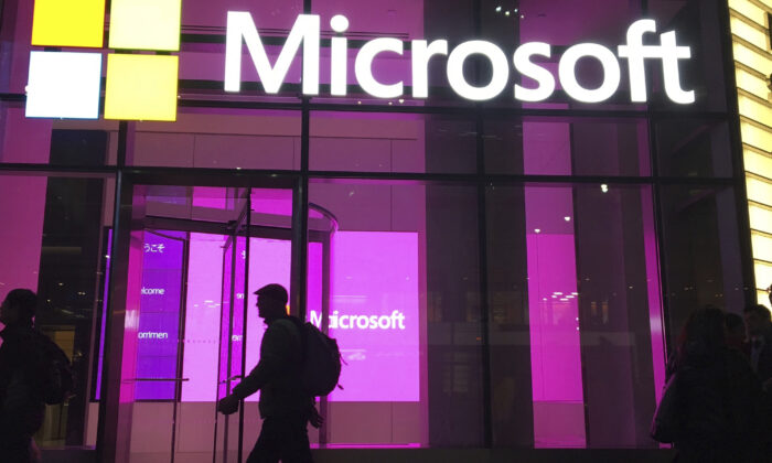 People walk past a Microsoft office in New York on Nov. 10, 2016. China-based government hackers have exploited a bug in Microsoft's email server software to target U.S. organizations, the company said Tuesday, March 2, 2021. (Swayne B. Hall/AP Photo File)