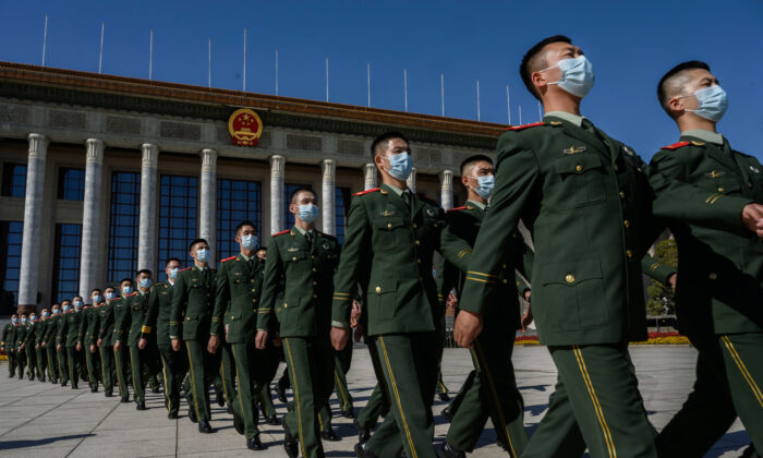 Chinese soldiers from the People's Liberation Army wear protective masks as they march after a ceremony marking the 70th anniversary of China's entry into the Korean War, at the Great Hall of the People in Beijing, China, on Oct. 23, 2020. (Kevin Frayer/Getty Images)
