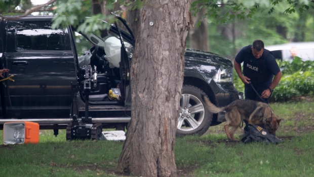 An RCMP officer works with a police dog as they move through the contents of a pick up truck on the grounds of Rideau Hall in Ottawa, on July 2, 2020.  (Adrian Wyld/ The Canadian Press)