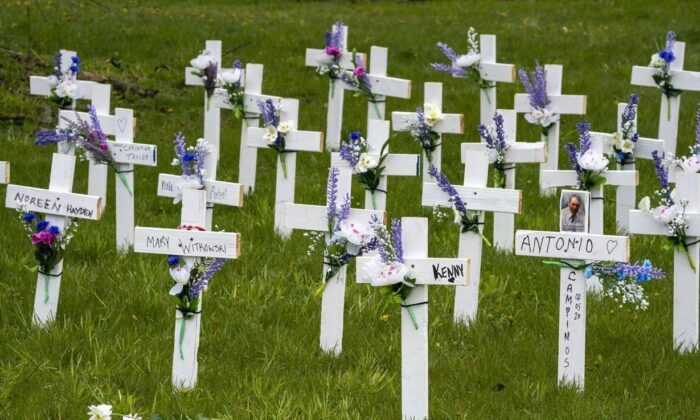 Flowers rest in front of crosses placed to remember the residents of Camilla Care Community who have lost their lives to COVID-19, in Mississauga, Ont. on May 11, 2020. Provisional estimates from Statistics Canada suggest nearly 14,000 more deaths than expected took place last year, even accounting for the pandemic and an aging population. (Frank Gunn/ The Canadian Press)