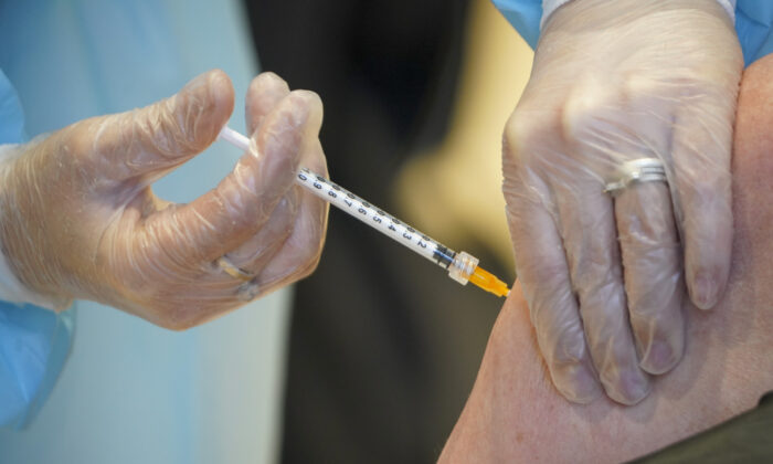 """A woman receives a COVID-19 vaccine, at the convention center known as """"La Nuvola,"""" The Cloud, in Rome, on March 10, 2021. (Andrew Medichini/AP Photo)"""