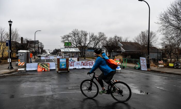 "A woman rides past the barricades of the ""autonomous zone"" near where George Floyd died in May 2020, in Minneapolis, on March 10, 2021. (Chandan Khanna/AFP via Getty Images)"