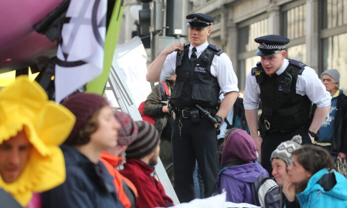 Police officers talk to Extinction Rebellion activists occupying Oxford Circus in the busy shopping district of central London on April 18, 2019. (Isabel Infantes/AFP via Getty Images)