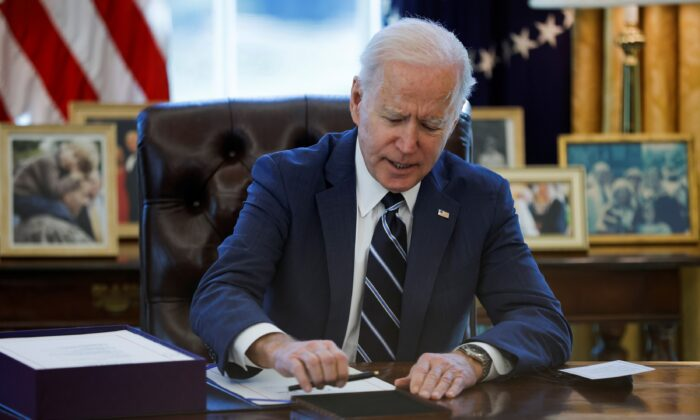 President Joe Biden signs the American Rescue Plan inside the Oval Office at the White House on March 11, 2021. (Tom Brenner/Reuters)