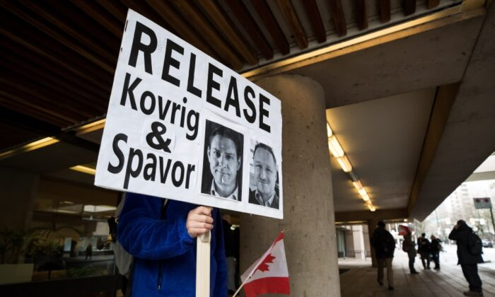 A man holds a sign calling for the release of Michael Kovrig and Michael Spavor outside B.C. Supreme Court where Huawei chief financial officer Meng Wanzhou was attending a hearing, in Vancouver on Jan. 21, 2020. (Darryl Dyck/The Canadian Press)