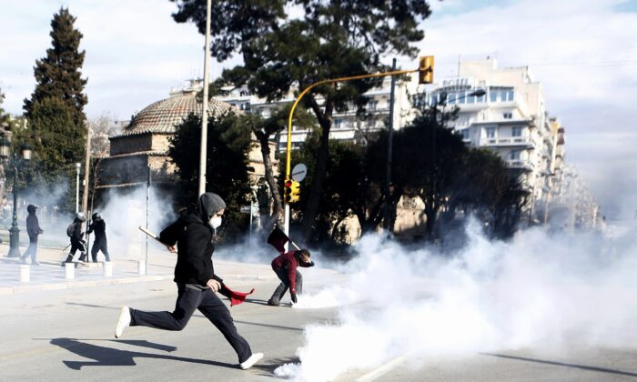 A protester kicks a gas canister back to riot police during clashes in the northern city of Thessaloniki, Greece, on March 11, 2021. (Giannis Papanikos/AP Photo)