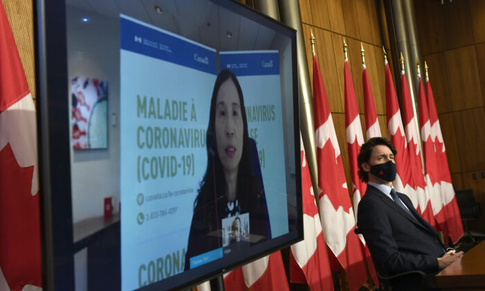 Prime Minister Justin Trudeau listens as Chief Public Health Officer of Canada Dr. Theresa Tam speaks via video conference during a news conference on the COVID-19 pandemic in Ottawa, Canada, on March 12, 2021. (Justin Tang/The Canadian Press)