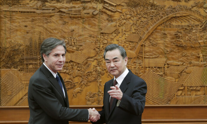 (L-R) Antony Blinken, who was then the U.S. Deputy Secretary of State, shakes hand with Chinese Foreign Minister Wang Yi at the Olive Hall in Beijing, on Feb. 11, 2015. (Andy Wong-Pool/Getty Images)
