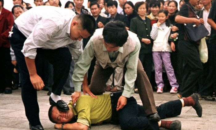 Two plainclothes police officers arrest a Falun Gong practitioner at Tiananmen Square in Beijing, on Dec. 31, 2000. (Chien-min Chung/AP Photo)