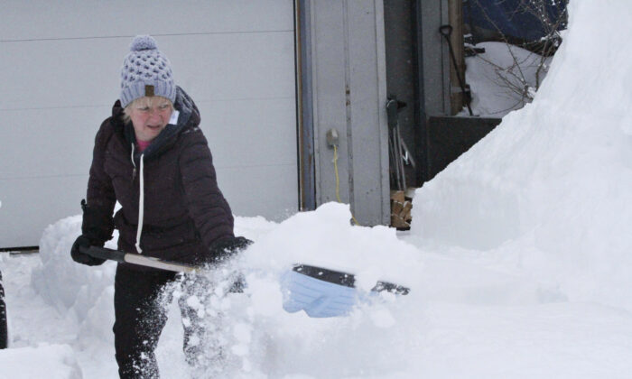 Judi Westfall shovels snow at her home in Anchorage, Alaska, on March 11, 2021. (Mark Thiessen/AP Photo)