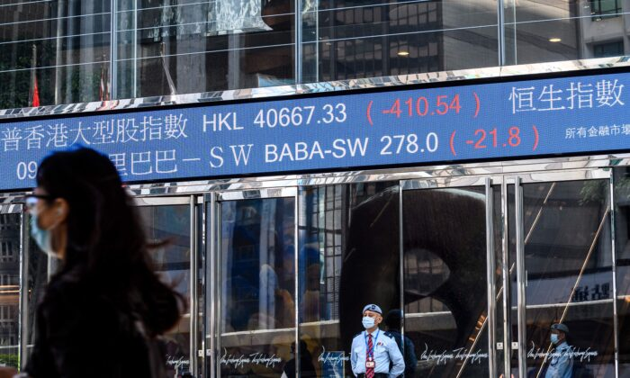 Stock activity of Alibaba Group Holding Ltd (BABA-SW) (top C) is displayed above a security guard as he stands outside the Exchange Square towers in Hong Kong on Nov. 4, 2020. (Anthony Walllace/AFP via Getty Images)