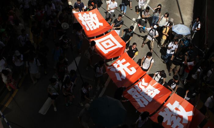 "Demonstrators display a banner reading ""withdraw brainwashing education"" during a protest against the government's efforts to implement national education in Hong Kong on July 29, 2012.  (Dale de la Rey/AFP/GettyImages)"