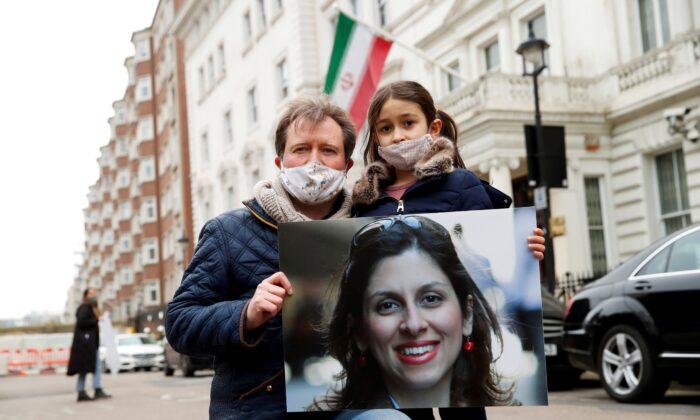 Richard Ratcliffe, husband of British-Iranian aid worker Nazanin Zaghari-Ratcliffe, and their daughter Gabriella protest outside the Iranian Embassy in London on March 8, 2021. (Andrew Boyers/Reuters)