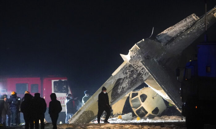 Emergency employees work at the side of the crashed Soviet-built An-26 two-engine turboprop at the airport of Kazakhstan's largest city, Almaty, Kazakhstan, on March 13, 2021. (Vladimir Tretyakov/AP Photo)