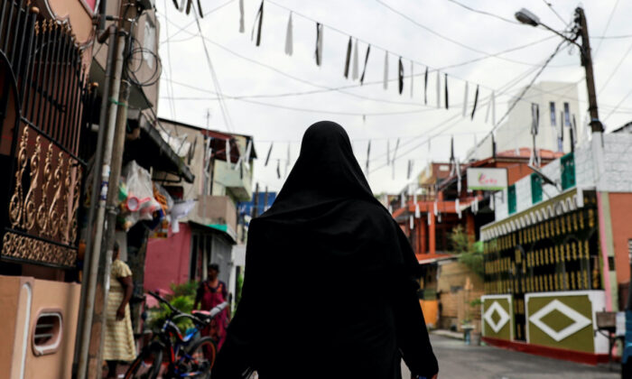 A Muslim woman wearing a hijab walks through a street near St Anthony's Shrine, days after a string of suicide bomb attacks across the island on Easter Sunday, in Colombo, Sri Lanka, on April 29, 2019. (Danish Siddiqui/Reuters)