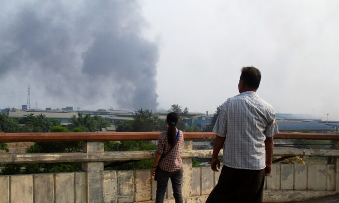 People look at smoke believed to be from a factory fire during the security force crack down on anti-coup protesters at Hlaingthaya, Yangon, Burma, on March 14, 2021. (Stringer/Reuters)