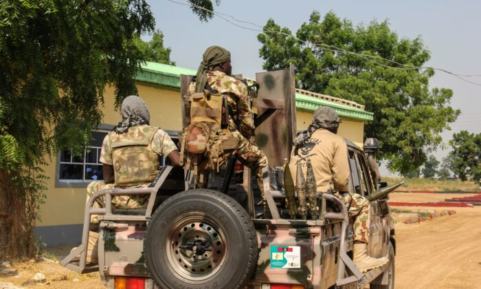 Nigerian Army soldiers are seen driving on a military vehicle in Ngamdu, Nigeria, on Nov. 3, 2020. (Audu Marte/AFP via Getty Images)