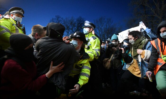 Police officers scuffle with people gathering at a band-stand where a planned vigil in honour of alleged murder victim Sarah Everard was cancelled due to Covid-19 restrictions, on Clapham Common, south London on March 13, 2021. (Justin Tallis/AFP via Getty Images)