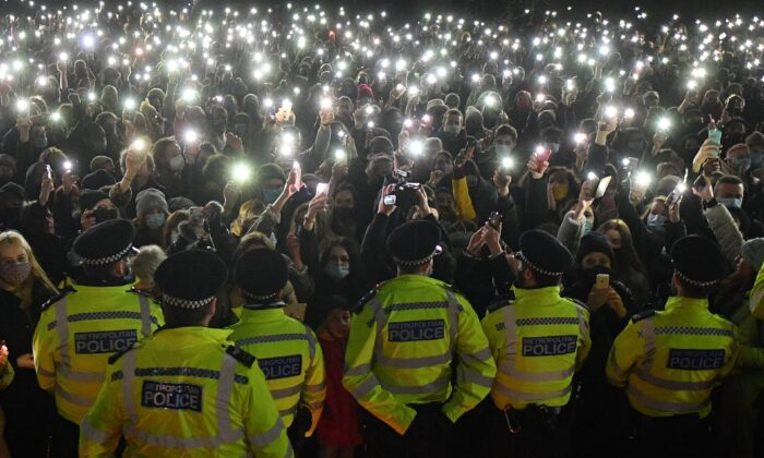 Police officers form a cordon as a crowd turn on their phone torches at a band-stand where a planned vigil in honour of murder victim Sarah Everard was cancelled due to CCP virus restrictions, on Clapham Common, south London on March 13, 2021. (Justin Tallis/AFP via Getty Images)