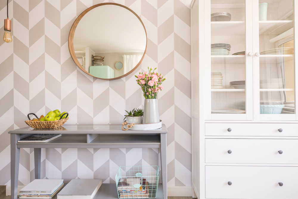 Mirror,On,Patterned,Wallpaper,Above,Grey,Table,With,Flowers,In