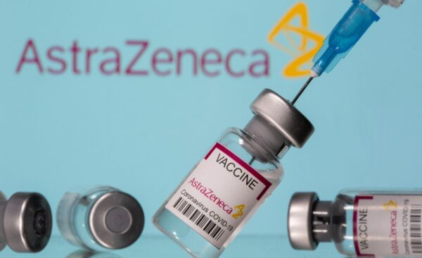"""Vials labelled """"Astra Zeneca COVID-19 Coronavirus Vaccine"""" and a syringe are seen in front of a displayed AstraZeneca logo in this illustration photo"""