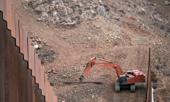 Construction crews work on a new section of the U.S.-Mexico border fencing at El Nido de las Aguilas, eastern Tijuana, Baja California state, Mexico, on Jan. 20, 2021. (Guillermo Arias/AFP via Getty Images)
