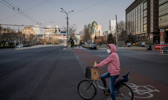 A woman wearing a mask sits on her bicycle at a red light on a nearly empty street in Beijing on March 22, 2020. (Nicolas Asfouri/AFP via Getty Images)