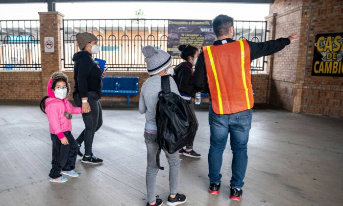 A city worker gives instructions to migrants at a bus station in Brownsville, Texas before travelling to meet relatives or sponsors on March 2, 2021. (Sergio Flores/AFP via Getty Images)