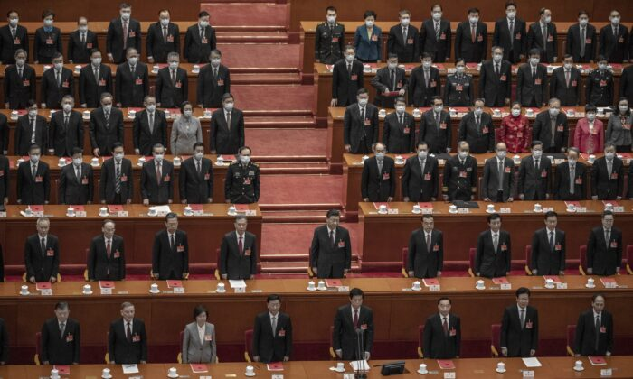 Chinese leader Xi Jinping (center) and lawmakers stand for the anthem during the closing session of the rubber-stamp legislature's conference at the Great Hall of the People in Beijing, China, on March 11, 2021. (Kevin Frayer/Getty Images)