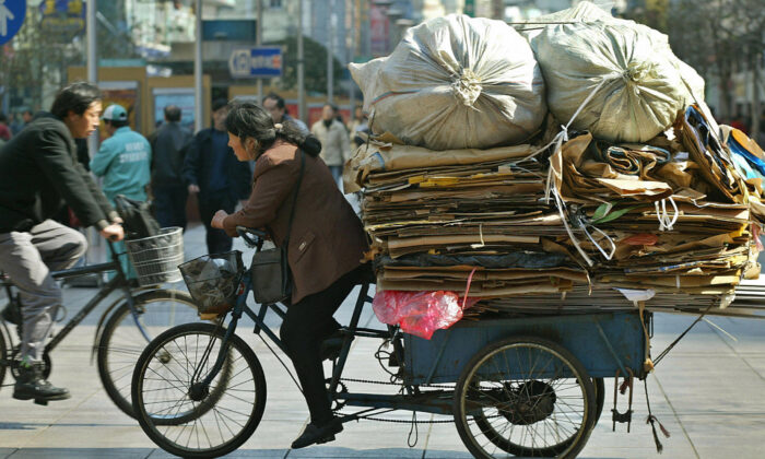 A migrant worker rides a tricycle full of waste along a street in Shanghai, China on Feb. 18, 2003. (Liu Jin/AFP via Getty Images)