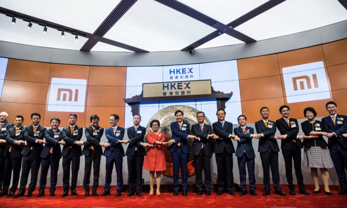 Xiaomi founder, Lei Jun (centre L-orange tie) joins hands with other executives at the company's initial public offering launched on the HKSE in Hong Kong on July 9, 2018. (Isaac Lawrence/AFP via Getty Images)
