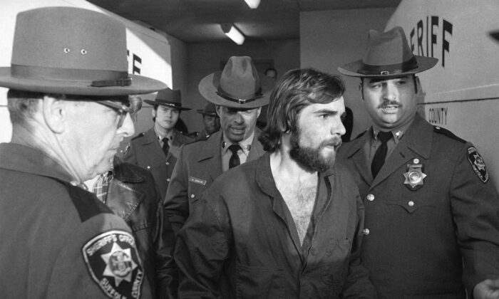 Ronald DeFeo Jr., center, leaves Suffolk County district court after a hearing in Long Island, N.Y., on Nov. 15, 1974. (Richard Drew/AP Photo)