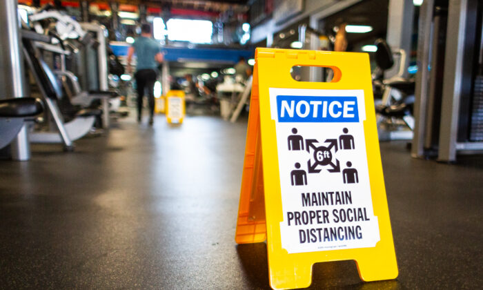 A sign on the floor of World Gym Fitness Center in Tujunga, Calif., on Jan. 5, 2021. (John Fredricks/The Epoch Times)