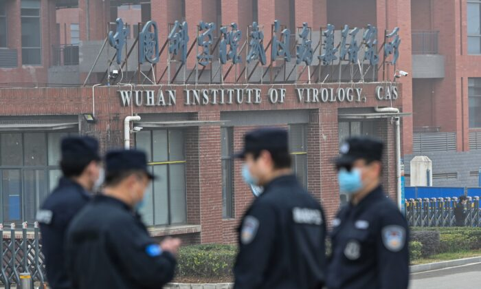 Security personnel stand guard outside the Wuhan Institute of Virology in Wuhan as members of the World Health Organization team investigating the origins of the CCP virus make a visit to the institute in Wuhan, China, on Feb. 3, 2021. (Hector Retamal /AFP via Getty Images)