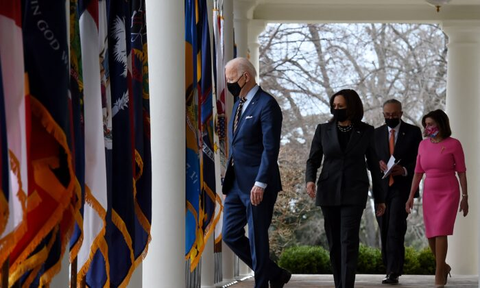 President Joe Biden, with (L-R) Vice President Kamala Harris, Senate Majority Leader Chuck Schumer (D-N.Y.), and House Speaker Nancy Pelosi (D-Calif.), arrives to speak about the American Rescue Plan in the Rose Garden of the White House in Washington, on March 12, 2021. (Olivier Douliery/AFP via Getty Images)