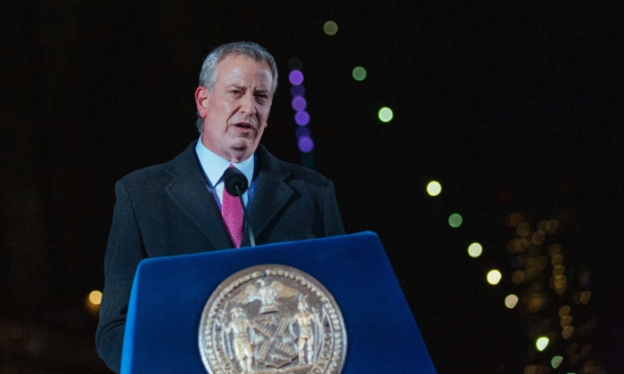 New York Mayor Bill De Blasio speaks as images of COVID-19 Victims are projected over the Brooklyn bridge as the city commemorates a COVID-19 Day of Remembrance in Brooklyn, New York on March 14, 2021. (Kevin Hagen/POOL/AFP via Getty Images)