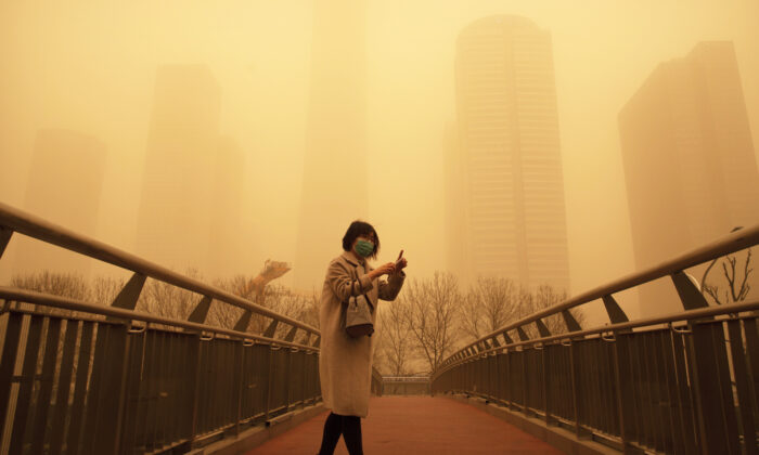 A woman walks along a pedestrian bridge amid a sandstorm during the morning rush hour in the central business district in Beijing on March 15, 2021. (Mark Schiefelbein/AP)