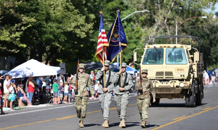 A military honor guard walks down the street to open the Provo Freedom Festival Parade in Provo, Utah, on July 4, 2018.  (George Frey/Getty Images)