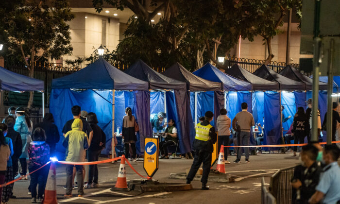 Residents receive mandatory COVID-19 test by health worker in an area under lockdown on Robinson Road at night in the mid-levels neighborhood in Hong Kong, China, on March 13, 2021. (Anthony Kwan/Getty Images)