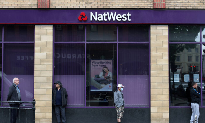 People maintain social distance while they queue outside a Natwest bank in Wimbledon in London, Britain, on May 1, 2020. (Hannah McKay/Reuters)
