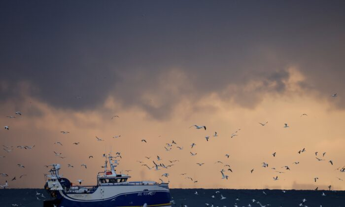 """Fishermen fish aboard the Boulogne-sur-Mer based trawler """"Manureva"""" in the North Sea, off the coast of northern France, on Dec. 7, 2020. (Pascal Rossignol/Reuters)"""